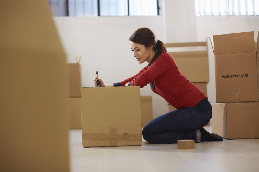 Lady packing up a package in her living room