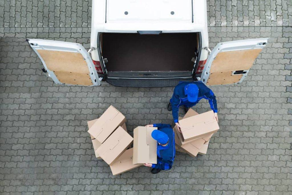 Employees storing boxes into van